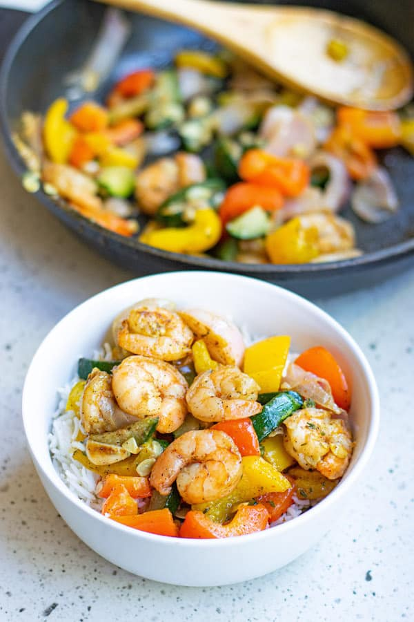 Garlic Thyme Shrimp and Veggies in white bowl with rice and sautee pan in background