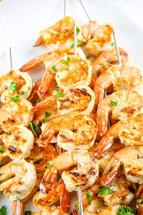 Grilled Lemon Shrimp Skewers on metal skewers stacked on white plate
