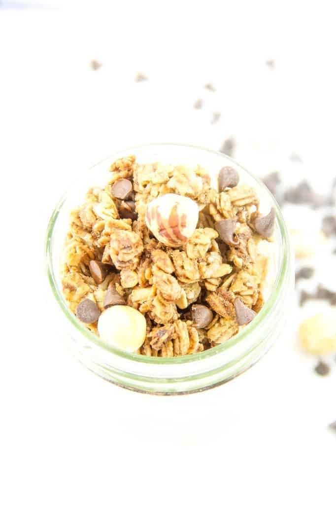Chocolate Hazelnut Granola in glass jar topped with hazelnuts and chocolate chips