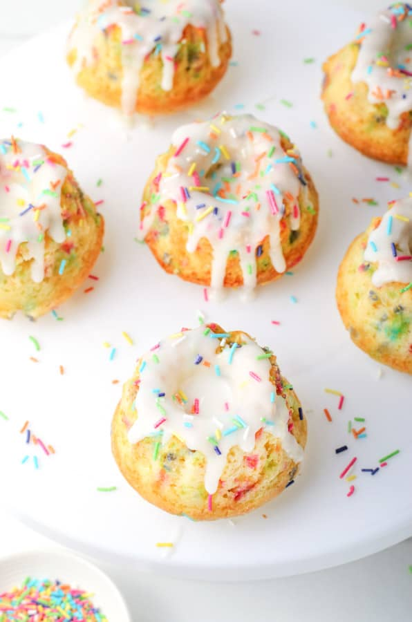 Funfetti Mini Bundt Cakes on white plate with sprinkles