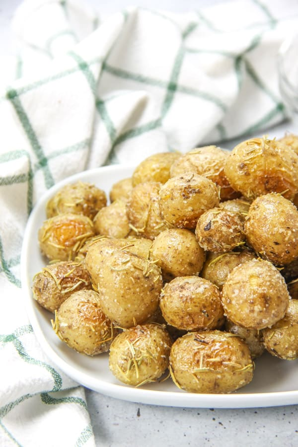 Roasted Rosemary Potatoes on white plate with green and white napkin