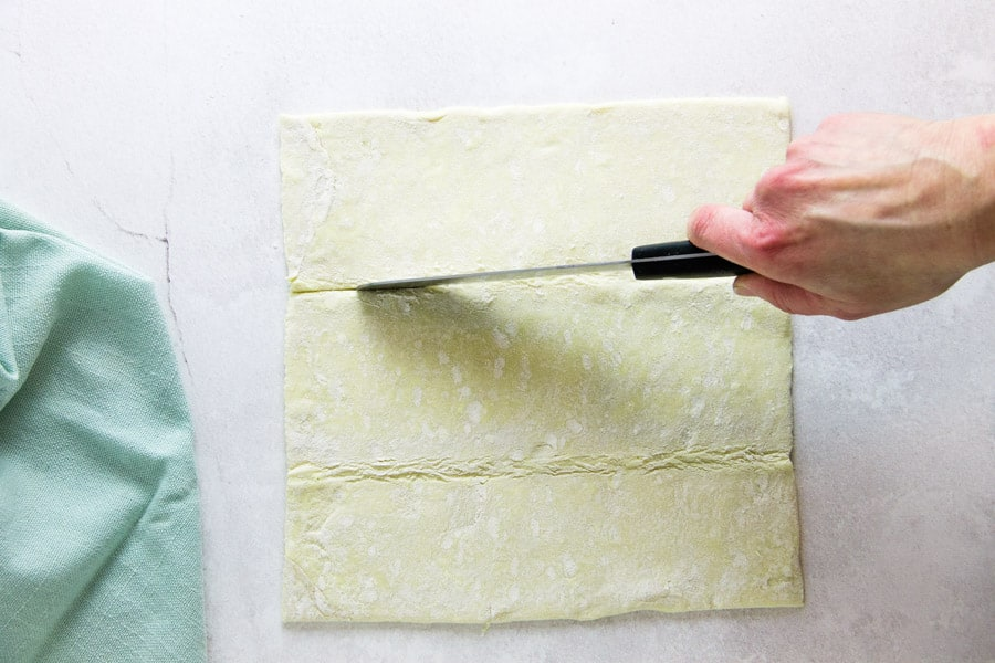 using knife to cut strips in puff pastry dough.