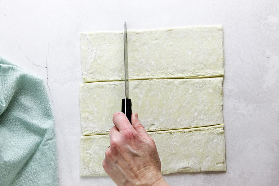 using knife to cut squares in puff pastry dough.