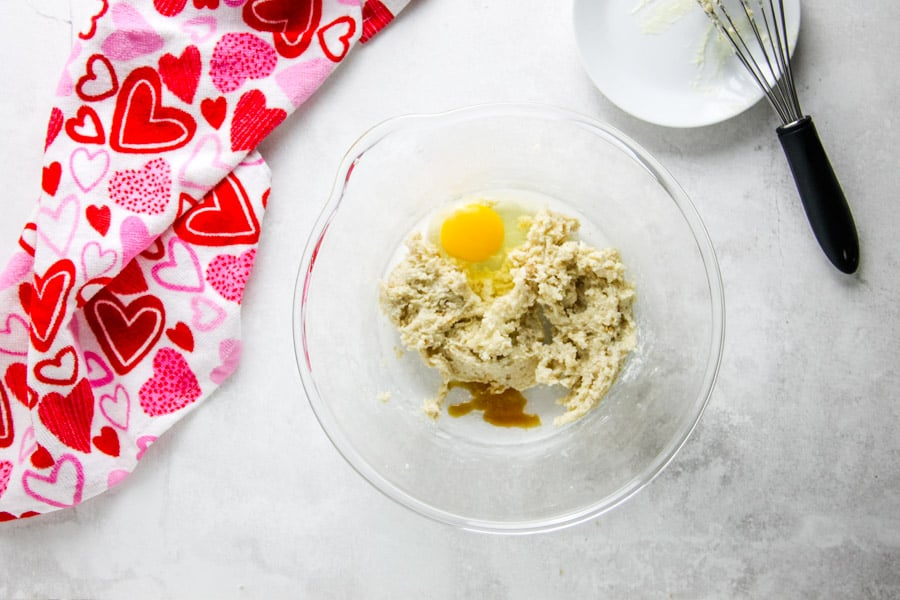 uncooked cookie ingredients in glass bowl with egg and vanilla